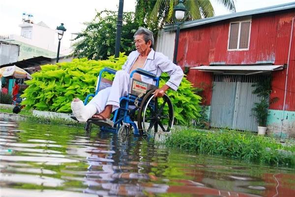 Một ông cụ đi xe lăn gặp nhiều khó khăn khi di chuyển trong nước ngập. Ảnh: NT
