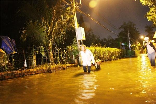 Một ông cụ vất vả đi làm về trong dòng nước lớn. Ảnh: NT