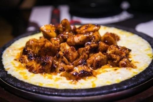 """Gà nướng phô mai chinh phục những tín đồ ăn vặt Sài Gòn chỉ trong một thời gian ngắn nhờ vào thịt gà cay """"không đỡ nổi"""" và lớp phô mai dẻo thơm lừng. Ăn kèm với cơm rong biển và bắp cải trộn, thịt gà được lóc xương sẽ ngon gấp bội phần khi kết hợp cùng phô mai nóng.(Ảnh: Internet)"""