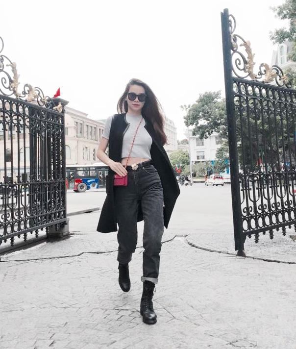 Hồ Ngọc Hà mang đến sự bụi bặm, cổ điển khi chọn phối quần jeans baggy cùng áo hở eo tông xám. Cô khéo léo kết hợp bộ trang phục cùng áo khoác không tay dáng dài, giày bốtda cùng mắt kính đồng điệu tông đen. Trong khi đó, chiếc túi đeo chéo tông hồng nhỏ xinh lại trở thành điểm nhấn khá thú vị trên tổng thể.