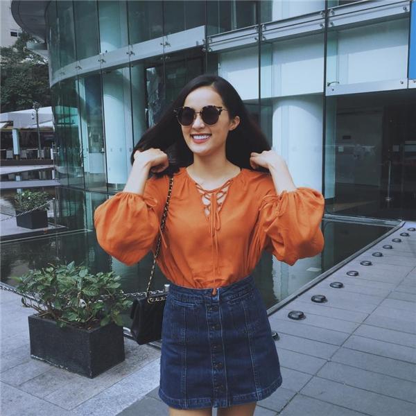 Chiếc áo tông cam giúp Hạ Vi nổi bật giữa chốn đông người. Cô nàng tiếp tục lăng xê chân váy denim cài cúc giữa.