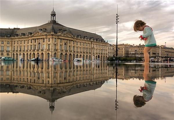 """Giữa lòngBordeaux, Pháp, một cậu bé đang chơi đùa với """"người bạn"""" giống hệt mình.(Ảnh: Guigurui)"""