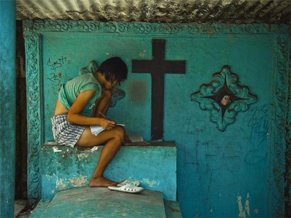 Một cô gái cặm cụi học bên ngôi mộ đá. (Ảnh: Flickr)