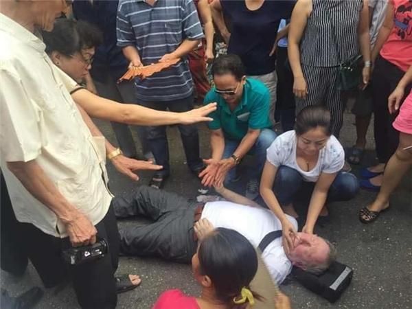 Vị khách Tây bị ngất giữa đường đang được người dân khu vực sơ cứu. (Ảnh:Internet)