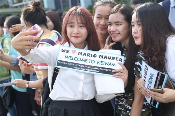 """Trên tay là những tấm áp phích có dòng chữ: """"We love Mario Maurer""""."""