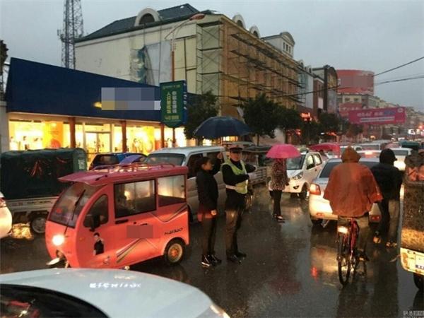 Hình ảnh đẹp về người phụ nữ che ô cho viên cảnh sát giao thông suốt 30 phút liền thu hút sự chú ý của cộng đồng mạng Trung Quốc. (Ảnh: NetEase)