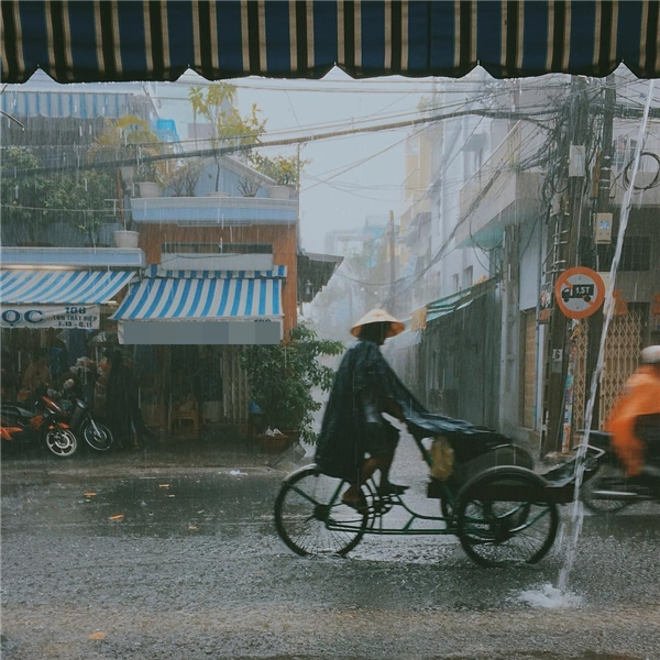 Sài Gòn mưa, những người lao động bé nhỏ vẫn xé màn mưa mà đi.(Ảnh: Âu Dương Thành)