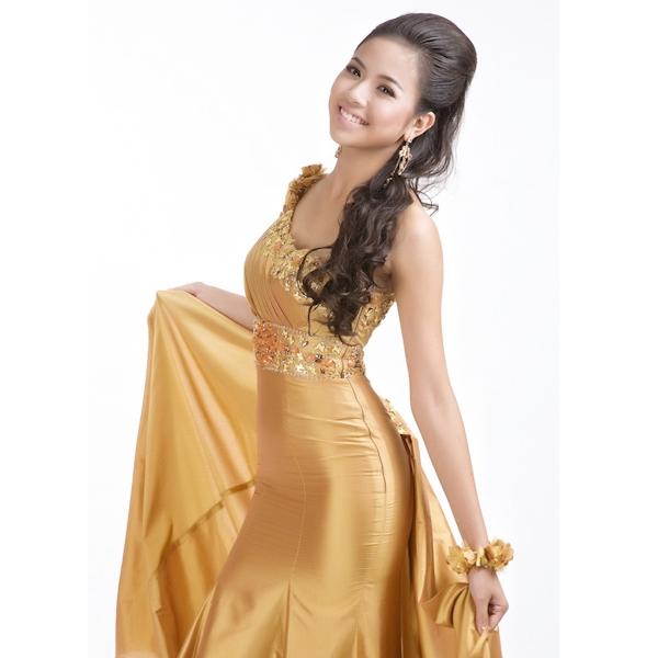 Dù hé lộ trang phục dạ hội sẽ có màu trắng nhưng trong đêm chung kết Hoa hậu Thế giới 2010, Kiều Khanh lại diện bộ váy lệch vai có tông màu vàng đồng. Phần đuôi váy rời giúp thiết kế trở nên bay bổng, nhẹ nhàng.