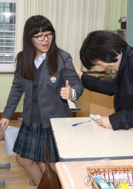 Một nữ thí sinh giơ ngón tay cái với cô giáo của mình tại trường Secho, thành phố Seoul sau khi tự chấm điểm cho mình với đáp án được công bố. Được biết kết quả chính thức sẽ có trong ngày 23/11 và thí sinh sẽ nhận được giấy báo vào ngày 2/12. (Ảnh: Internet)