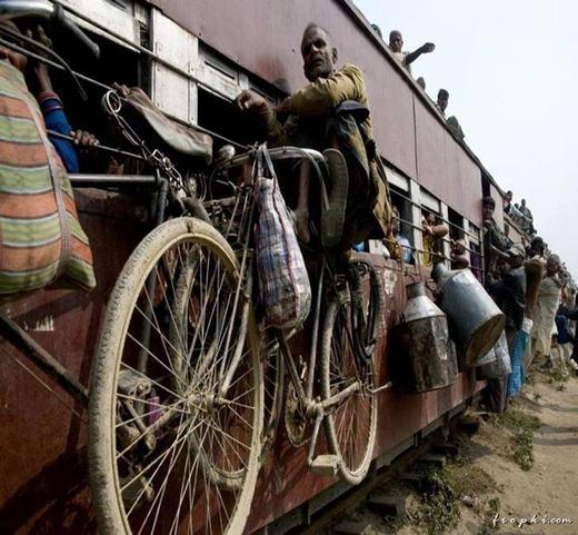 Một người đàn ông ngồi trên chiếc xe đạp được treo lơ lửng bên tàu hỏa. (Ảnh: Internet)