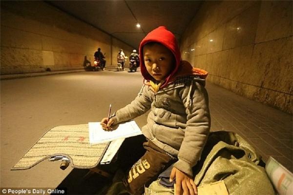 Lấy chiếc ghế gỗ nhỏ chông chênh làm bàn, Yihang đặt quyển vở lên rồi cứ thế chăm chú làm bài tập.(Ảnh: People's Daily Online)