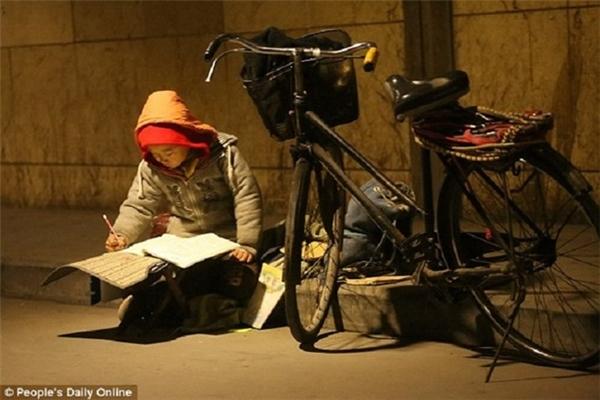 Bức ảnh cậu bé Li Yihang học dưới ánh đèn đường. (Ảnh: People's Daily Online)