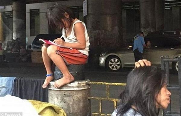Cô bé Philippines làm bài tập trên dải phân cách. (Ảnh: Internet)