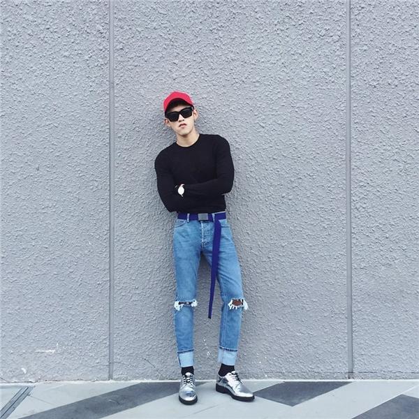 Chàng trai trẻ Dương Minh Tuấn kết hợp áo phông tay dài, phom rộng cùng quần jeans baggy cổ điển. Bộ trang phục thu hút hơn nhờ mũ lưỡi trai tông đỏ nổi bật, mắt kính gọng vuông cùng giày ánh bạc.