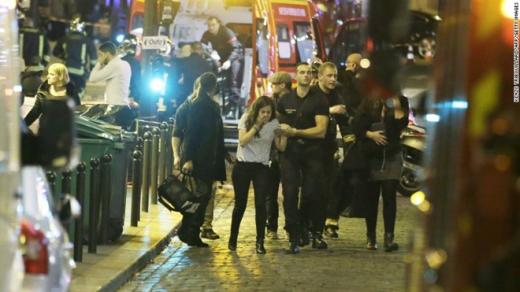 """Nhân viên an ninh dìu người phụ nữ đang hoảng sợ trong vụ khủng bốtại quận 10. """"Chúng ta sẽ đoàn kết và giữ bình tĩnh trong tình huống này. Nước Pháp cần chứng tỏ sự mạnh mẽ và vĩ đại"""", ông Hollande nói sau khi thủ đô Paris rung chuyển vì các vụ tấn công liên hoàn. Ảnh: Getty Image"""
