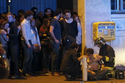Nhân viên cứu hộ đang băng bó cho nạn nhân bị thương bên ngoài nhà hát Bataclan, trong khi những người khác vẫn hoảng loạn sau sự việc. Theo nhà chức trách Pháp, lực lượng an ninh đã tiêu diệt các phần tử khủng bố tại nhà hát. Ảnh: New York Times