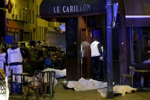 Thi thể nạn nhân được phủ bạtbên ngoài nhà hàng ở Paris. Ít nhất 4 nhân viên an ninh thiệt mạng trong vụ đánh bom liều chết. Ảnh: Reuters