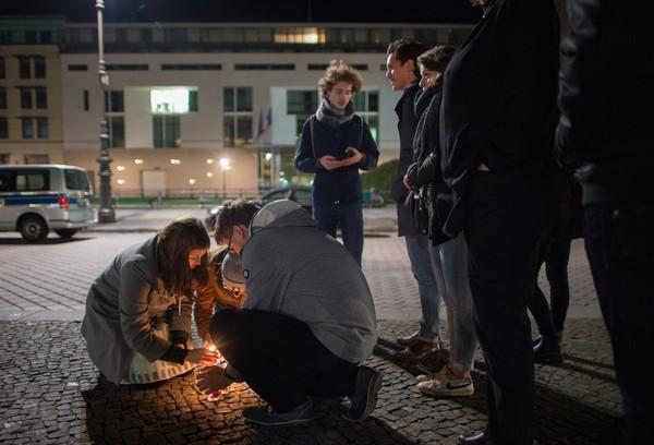 Dân Đức quây quần đốt nến tưởng niệm các nạn nhân xấu số trong vụ thảm sát phía bên ngoài Đại sứ quán Pháp ở thành phố Berlin.