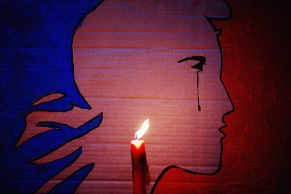 """Nến được thắp lên trước bức tranh """"Nước Pháp đang khóc"""" tại quảng trường Aotea, thành phố Auckland, New Zealand."""