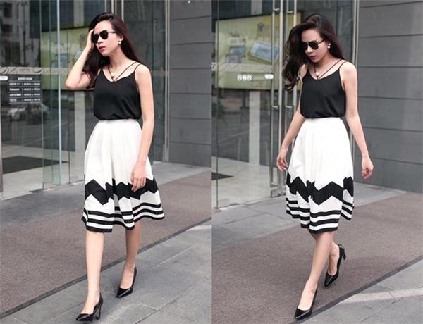 Bà mẹ sinh năm 1983 diện áo hai dây trẻ trung, phối váy xòe trắng, họa tiết tối màu ăn nhập. Giày gót vuông cổ điển đi kèm tiệp màu.