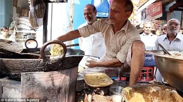 Ông Ram Babu dùng tay không đảo đồ ăn trong chảo dầu nóng. Ảnh: Daily Mail