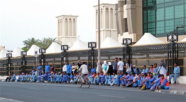 Nhóm công nhân chờ xe buýt để về khu vực sống tập trung, bỏ lại phía sau thành phố Dubai hoa lệ trong mắt khách du lịch. Ảnhh:Flickr.