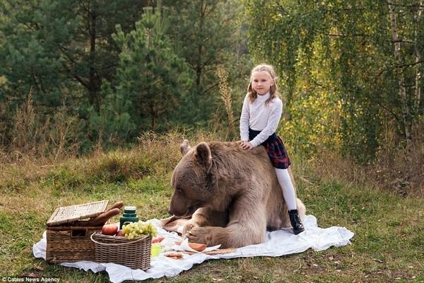 Dường như ông gấu cũng thương trẻ em, mặc cho cô bé vần vò cưỡi lên cưỡi xuống.