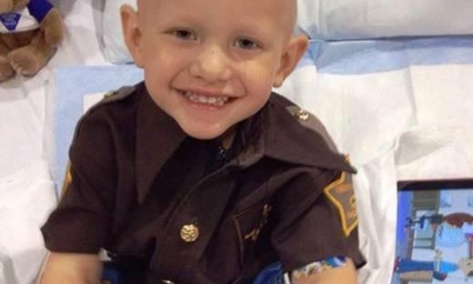 Cậu bé 3 tuổi cười hạnh phúc khi được nhậm chức cảnh sát ngay trên giường bệnh.(Ảnh: Internet)
