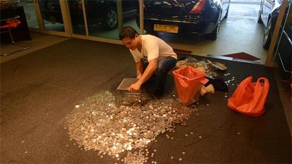 Nhân viên cửa hàng thu gom số tiền xu mang trả cho chủ nhân của nó. (Ảnh Internet)