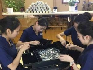 Các nhân viên cửa hàng trang sức đếm số tiền xu anh Liang dùng mua nhẫn. (Ảnh Internet)