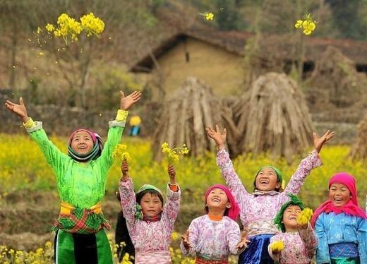 Em bé Sa Pa tung những cánh hoa cải cùng nụ cười hồn nhiên và vô tư. (Ảnh: Internet)