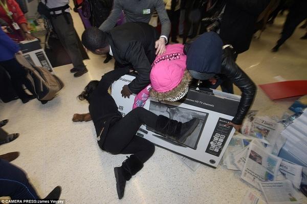 Một phụ nữ cố gắng nằm đè lên chiếc ti vi sau khi tranh giành với những khách hàng khác tại 1 cửa hàng Asda ở Wembley. Trong khi người phụ nữ nhất quyết nằm ôm chiếc ti vi, nhiều khách hàng khác cũng không chịu bỏ cuộc.
