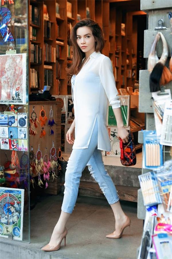 Vẫn với hai tông màu xanh, trắng, nữ ca sĩ lại mang đến vẻ ngoài thanh lịch hơn qua sự kết hợp giữa áo sơ mi dáng dài cùng quần jeans bó sát cổ điển. Thiết kế giúp Hồ Ngọc Hà phô diễn khéo léo đôi chân dài miên man đáng mơ ước.