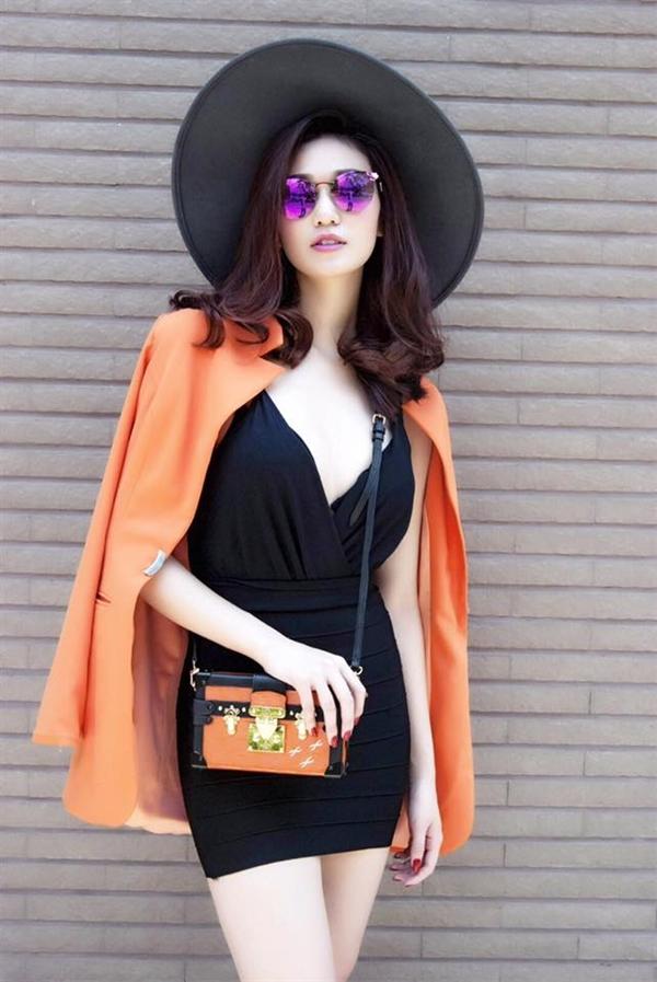 Khánh My vẫn trung thành với phong cách sang trọng, gợi cảm thường thấy. Những phụ kiện sắc cam đã góp phần tạo nên sự nổi bật cho tổng thể với gam đen huyền bí, cổ điển.
