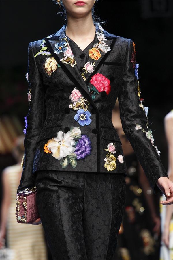 Những đóa hoa cẩm chướng đầy màu sắc rực rỡ trên nền đen của thiết kế suit cổ điển, thanh lịch.