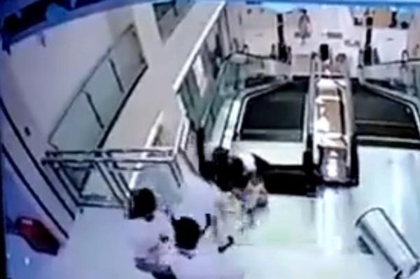 Hình ảnh người mẹ đã cố gắng cứu con trai ra khỏi thang cuốn. Ảnh: Internet