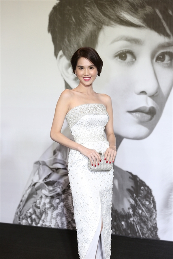 Trên thảm đỏ LYNK Fashion Show 2015, Ngọc Trinh tiếp tục ghi điểm nhờ bộ váy cúp ngực xẻ tà ôm sát với tông màu ánh bạc hợp mốt. Thiết kế vẫn sử dụng chi tiết đính kết làm điểm nhấn.