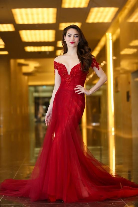 Bộ váy đỏ nổi bật tạo điểm nhấn bởi đường xẻ ngực sâu hút tinh tế. Thiết kế kết hợp giữa voan, lưới cùng ren được đính kết dọc theo phần ngực.