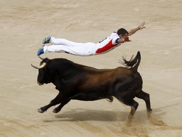 """Một """"recortador"""" nhảy qua lưng một con bò tót trong cuộc thi tại trường đấu bò Pamplona trong ngày thứ sáu của lễ hội San Fermin, phía bắc Tây Ban Nha, ngày 11/7/2015. Khác với các đấu sĩ, """"recortador"""" chỉ né tránh con bò và không sử dụng mũi lao hay gươm."""