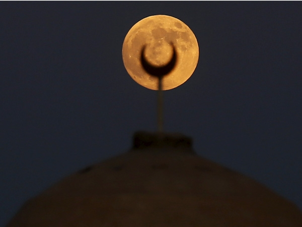 Siêu trăng trên ngọn tháp của nhà thờ Hồi giáo ở Wadi El-Rayan Lake, phía tây nam thủ đô Cairo, Ai Cập ngày 27/9/2015. Siêu trăng kết hợp với nguyệt thực tạo ra hiện tượng trăng máu, sáng hơn và lớn hơn bình thường.