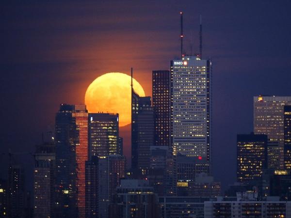 Trăng mọc đằng sau những tòa nhà cao tầng tại khu tài chính ở Toronto, 25/11/2015.