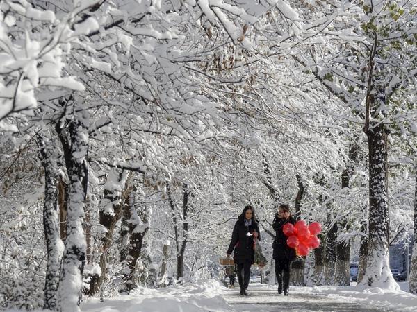 Hai phụ nữ đi bộ dọc theo một con đường phủ đầy tuyết ở Almaty, Kazakhstan ngày 16/11/2015.