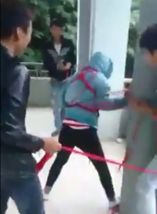 4 chàng trai đang cố gắng buộc chặt bạn vào cột. (Ảnh cắt từ clip)