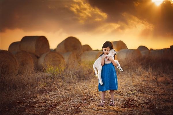 Thiên thần nhỏ cùng chú dê trắng. (Ảnh:Elena Paraskeva, Cyprus)