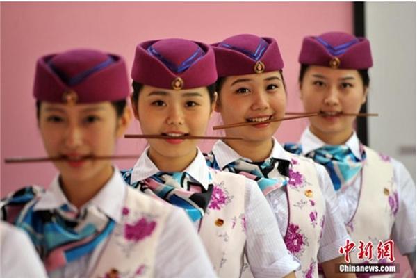 Các tiếp viên hàng không phải ngậm đũa để tập cười. (Ảnh: Chinanews)
