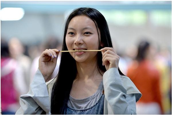 """Ngậm đũa để tập cười đã trở thành """"trào lưu"""" trong giới trẻ Trung Quốc. (Ảnh: Internet)"""