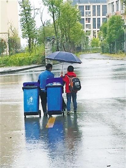 Cậu bé tốt bụng Jian Xiđã che ô, kéo rác giúpngười phụ nữ lao công giữa trời mưa to tầm tã. (Ảnh Internet)