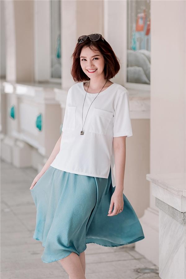 Trúc Diễm mang đến vẻ ngoài cổ điển, thanh lịch qua sự chọn phối giữa áo phông phom rộng cùng chân váy xòe nhẹ nhàng tông màu xanh lơ pastel. Chất liệu vải nhẹ nhàng, mịn màng càng tôn lên nét quyến rũ của người đẹp.