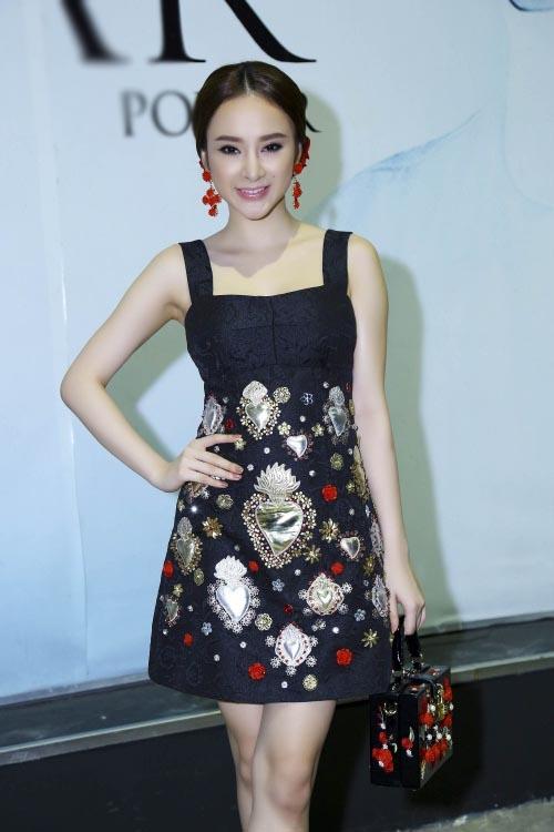Angela Phương Trinh búi tóc cao với phụ kiện hoa ton-sur-ton với trang phục và túi xách.