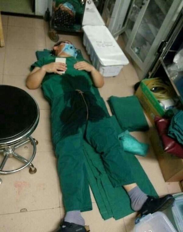 Bức ảnh chụp lại khoảnh khắc anh đang mặc bộ đồ phẫu thuật ngủ thiếp ngay tại phòng mổ. (Ảnh Internet)